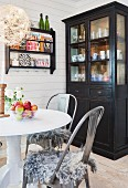 Dark display cabinet, round table, vintage chairs and shelves of ornaments on white wooden wall