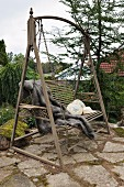 Antique garden swing with animal-skin blanket and scatter cushions on terrace with old, mossy, crazy paving