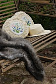 Sun hat, two old-fashioned embroidered cushions and fur blanket on antique garden swing