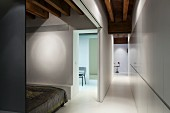 Sleeping area behind open sliding doors opposite white fitted cupboards in minimalist interior
