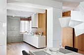 Blick über Essplatz in offene Küche mit weißem, minimalistischem Küchenblock und passendem Dunstabzug vor Holzwand
