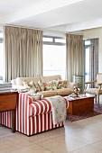 Sofa mit rot-weissen Streifen und hellem Bezug um Holztruhe, im Hintergrund bodenlange Vorhänge an Fensterfront in Wohnzimmer