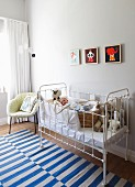 Wicker bassinet in white vintage cot, fifties-style armchair and blue and white striped rug in nursery