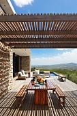 Schlichte, moderne Outdoor Möbel unter Pergola mit Holzlamellen auf grosszügiger Terrasse, vor Natursteinhaus