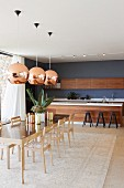 Pendant lamps with copper-coloured lampshades above dining set with long designer table and chairs made from pale wood; kitchen with free-standing counter in background