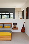Double bed with grey and yellow bed linen and minimalist bedside cabinet on white half-height wall; ensuite bathroom in background