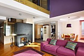 Modern violet couch in open-plan interior with dining area and fireplace in partition wall below mezzanine