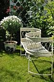 Delicate, white, metal garden kissing seat on lawn