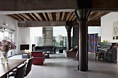 Loft apartment with black metal pillar under girder structure, dining area to one side and lounge area with leather retro armchairs