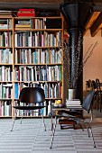 Black, retro-style chairs in front of bookcase and black metal column to one side in loft apartment