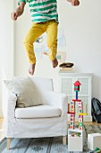 Boy bouncing on armchair in living room