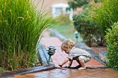 Toddler playing on paved garden path