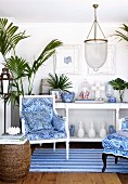 Armchairs with blue and white covers on striped rug in front of white console table in maritime ambiance