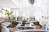 Ecru sofa set around white coffee table in double-height interior with closed window shutters