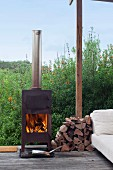 Fire in log-burner next to small pile of firewood on terrace, pale couch to one side and view into densely planted garden