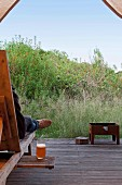 Wooden lounger with drinks shelf and barbecue on wooden terrace with view into wild garden