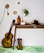 Guitar leaning against wooden console table decorated with vintage bottle, net bag and hat; picture of trees projected on floor