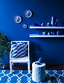 Blue and white arrangement of wicker chair, side table and vases on shelves