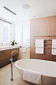 Bathroom with light wood paneling, stone tile floor and modern free-standing bath tub