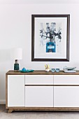 Sideboard with wooden casing and white-painted doors under framed picture on wall