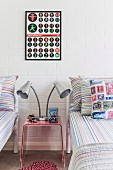 Table lamp with two heads on plexiglas bedside table between twin beds below framed poster on whitewashed brick wall