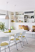 White dining table, chairs with seat cushions, pendant lamps with slatted lampshades and cushions on bench in background below wall-mounted shelves