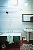 Vintage-style bathtub next to pedestal sink against white-tiled wall; historical ambiance