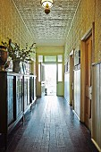 Antique sideboard on wooden floor and walls and ceiling covered in ornamental metal tiles in long narrow hallway