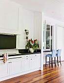 Küchenzeile mit dunkler Arbeitsplatte und weissen Unterschränken, seitlich Theken Sitzplatz auf eleganter Veranda mit Holz Dielenboden
