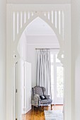 White-painted ogee arch built into doorway and view of comfortable armchair in front of French windows