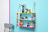 Colourful, hand-made shelves with wooden beads threaded on climbing ropes and hung from metal rings