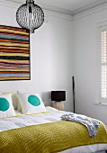 Splashes of colour in white bedroom, wall-hanging above double bed and scatter cushions