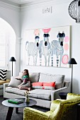 Little girl on sofa below picture of zebras and shiny gold velvet armchair