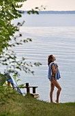 Woman wearing bikini and holding towel on shore of calm lake