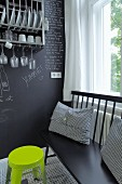 Black bench with scatter cushions and neon yellow stool against chalkboard wall