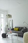 Dekokissen auf grauem Retro Sofa vor geweisselter Ziegelwand in Wohnraum mit traditionellem Flair