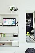 Flatscreen TV above drawers in modern, white media cabinet