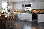 Wooden dining table and chairs on marbled tiled floor and white fitted kitchen with incorporated window