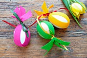 Easter decorations - eggs decorated with strips of colourful felt on wooden surface