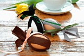 Easter decorations - eggs decorated with strips of dark felt on rustic wooden surface