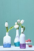Bottles painted white, decorated with glitter and used as vases for white tulips in front of turquoise wall