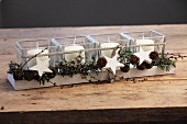 Tealight holders with Advent arrangement of cones and white wooden stars in long wooden tray