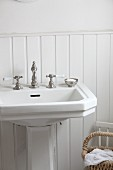 Pedestal washbasin with vintage tap fittings against white wainscoting