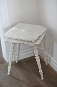Lace-edged cushion on vintage stool with turned legs