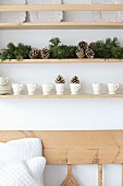Arrangement of conifer branches and cones amongst white china on shelves above wooden bench