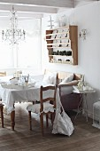Vintage-style dining area below crystal chandelier and rustic plate rack on wall