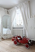 Red ride-on car on wooden floor in white, shabby-chic bedroom with window and cheval mirror in background