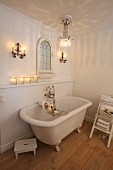 Romantic bathroom with crystal chandelier and free-standing claw-foot bathtub in candlelight