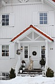 White clapboard country house with dog sitting in porch