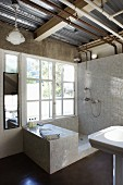 Rustic bathroom with tiled shower area next to large window below exposed utility lines in ceiling space